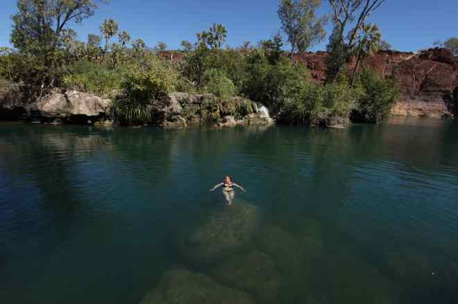 Christina taking a swim at Indarri Falls. The white stacks behind are tufa formations, like at Mono Lake in CA